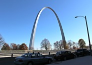 The St. Louis Gateway Arch stands tall admist busy traffic and a beautiful city, signifying our country's past expansion to the West.